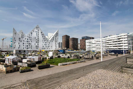 Modern architecture with appartment buildings at the docks in Aarhus, Denmark. In front wooden boxes that the owners of the apartments grow their flowers and herbs. Editorial