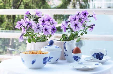 Mesa redonda com um pano de mesa branco pronto para o café da manhã. 2 flores roxas de petúnia em vasos de flores brancas e porclain branco, decoradas com flores azuis. Uma tigela cheia de cereais e uma colher, um copo de café, um prato lateral e um ovo cozido. Tudo pronto Foto de archivo - 79806034