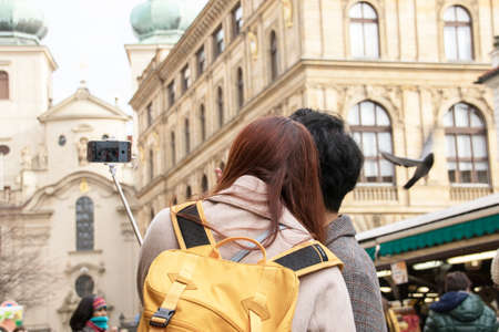 Couple taking their selfie in the center of Prague, the Czech Republic. Female with red hair, wearing a beige coat and a yellow rucksack. In the background one of Prague's many churches with two copper spires
