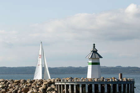 The top of the white sails on a sailboat, at the entrance to the harbor in ebeltoft, Denmark, with one of the lighthouses as a guide.