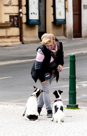 Young female wearing facial mask, during covid-19 lock down, training her two terriers close to a busy Street in Prague Center, The Czech Republic Europe