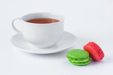 French multicolored cakes macarons and a cup of tea on a saucer on a white background