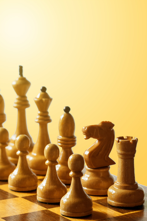 wooden chess pieces on a warm light background (toned, shallow depth of field)