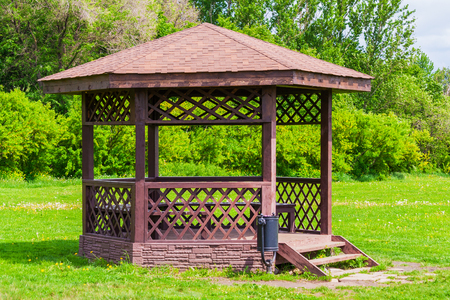 Wooden arbour in park, illuminated by sunlight a background of green trees (summer) Stock Photo