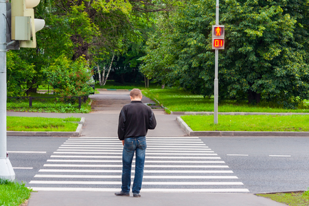 A man on a pedestrian crossing is waiting for the green light to move (concept, sign)