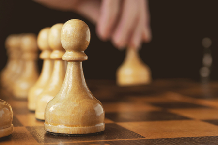 A hands of chess player makes a move the white pawn forward, out of focus, pawn on the foreground in focus (concept)