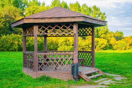 Wooden arbour in park a background of green lawn and trees
