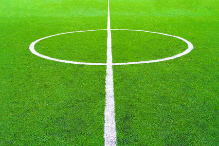 Perspective view of a central circle of green football field (background)