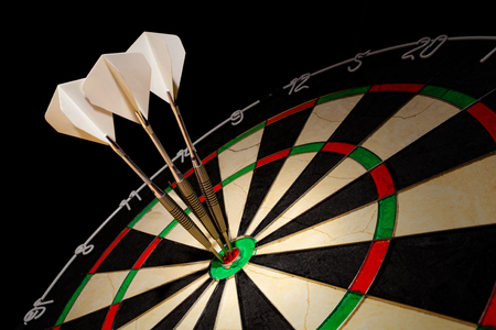 Sisal dartboard with three darts in a bullseye on a black background