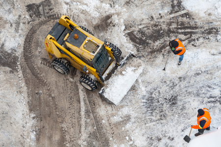 Top view of a snow-removing machine and workers in orange uniforms on a dirty road 스톡 콘텐츠