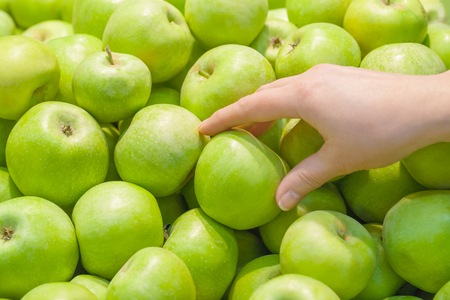 A female hand takes a green apple off the counter in a supermarket
