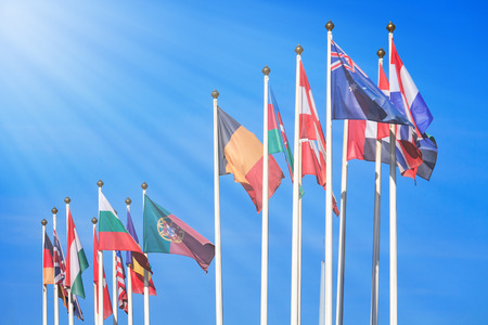 Flags of different countries illuminated by the rays of the sun against a bright blue sky Banque d'images