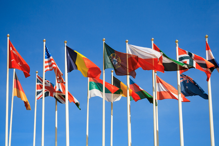 Rows of a flags of different countries of the world a background of clear blue sky