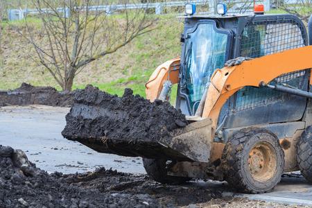 Works on the improvement of the park area. Skid steer loader transports the black soil