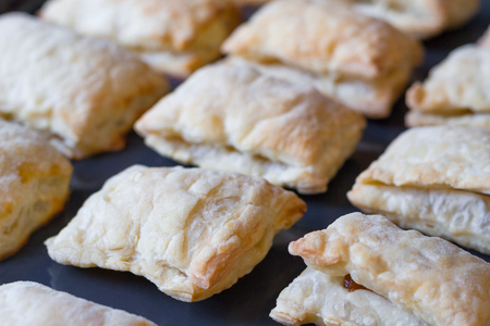 Close up view of a freshly baked pies made of puff pastry on a baking sheet (shallow depth of field) Stock Photo