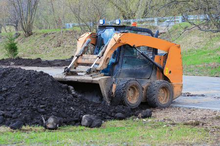 Works on the improvement of the park area. Skid  steer loader rakes black soil into bucket Foto de archivo