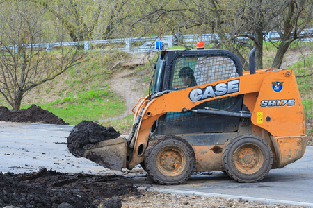 Moscow, Russia, april 2018: Works on the development of the park area. Skid steer loader transports black soil (editorial)