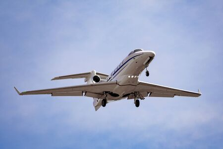 Light business jet flying in cloudy sky