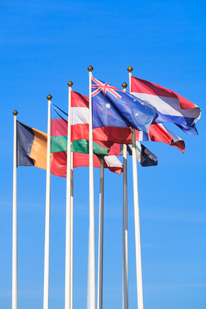 Flags of different countries, flutters in the wind, a background of clear blue sky