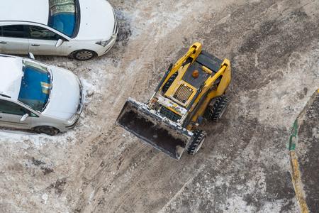 Vista dall'alto di una macchina sgombraneve e di un'auto parcheggiata su una strada sporca
