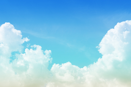 White cumulus fluffy clouds against a bright azure sky with copy space as background (toned)
