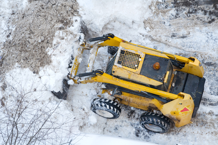 Aerial view of a snow-removing machine shoveling the snow from the road Foto de archivo