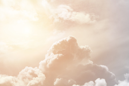Soft cumulus fluffy clouds illuminated by the sun against a orange sky (background, toned)