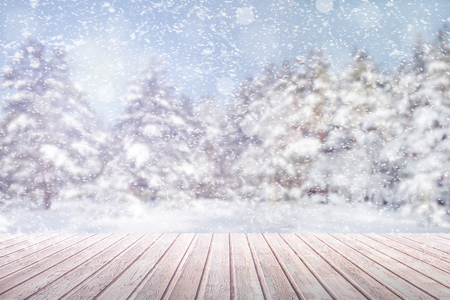 View on a brown wooden table against a winter forest in blur and snowfall (background, abstract, concept, copy space)