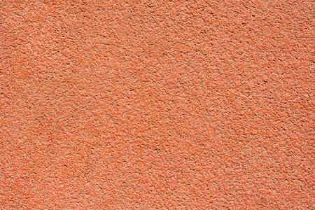 Superficie in tartan arancione di una pista da corsa come trama, sfondo