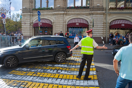 Moscow, Russia, August 2018: A man in light green protective vest regulates traffic at a pedestrian crossing in downtown (editorial) Editorial