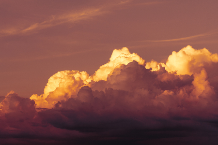 Dramatic view of a dark clouds in the evening sky illuminated by sunset Фото со стока