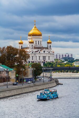 Moscow, Russia, August 2018: General view on a Cathedral of Christ the Savior and Bolshoy Kamenny Bridge over Moscow-river with a pleasure boat sailing below (editorial)