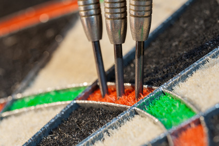 Close up view on three darts in triple sector of sisal dartboard