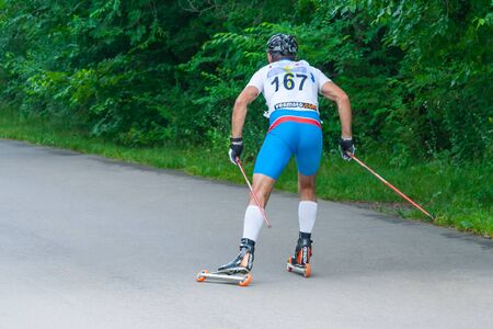 Back view of roller skater is on the road in park at the