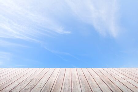 Perspective view on a wooden table top on a bright blue sky background