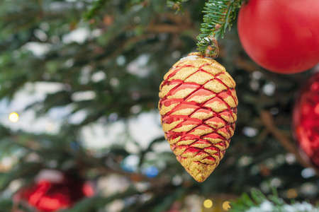 Close up view on a pine cone toy on the Christmas tree (shallow depth of field)