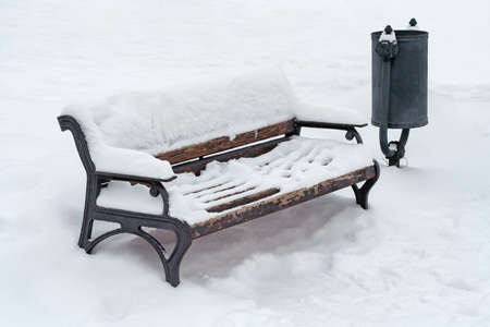Snow covered wooden bench and a trash can in the winter park