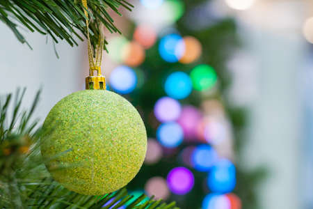 Close up view on a light green ball on a Christmas tree on a background of multicolored lights in bokeh (shallow depth of field)