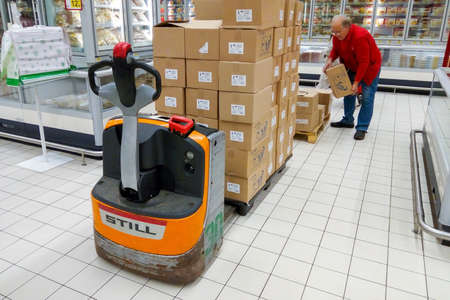 Moscow, Russia, August, 2017. An elderly supermarket worker unloads boxes from a forklift (editorial) 版權商用圖片