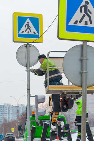 Moscow, Russia, December 2018. Workers in yellow uniforms installation a road sign on the pole. (editorial).