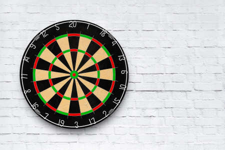 Dartboard is hanging on a white brick wall with copy space as texture, background (Interior Design) 版權商用圖片