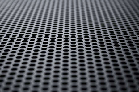 Perspective view on a the black metal surface with regular round holes. Industrial background (abstract)