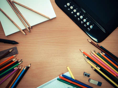 Photo of office tools, colored pencils and a graphics tablet on the table photo