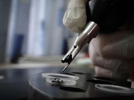 Tattoo artist at work. Closeup - tattoo machine and black ink 写真素材