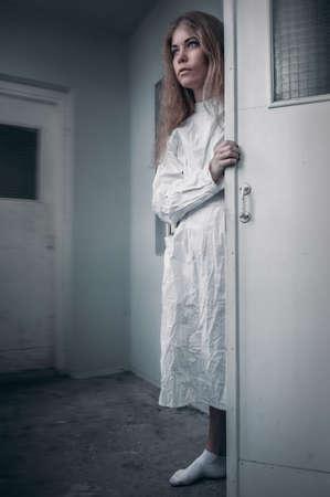 Fille malade mentale avec une camisole de force en psychiatrie Banque d'images - 92525356