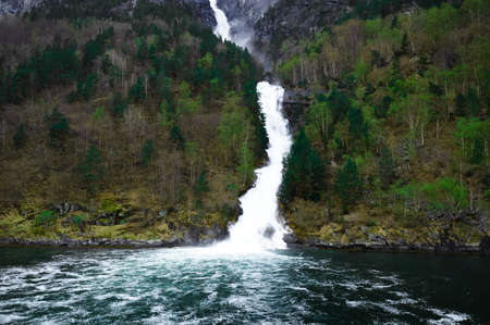 waterfall flows down among the mountains - Flam in Norway - fjords and the river