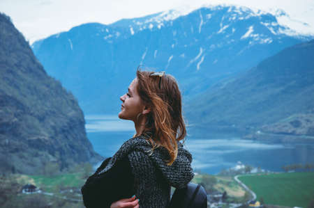 Young woman stands on the background of beautiful mountains and a lake, fjord flam Norway in spring season