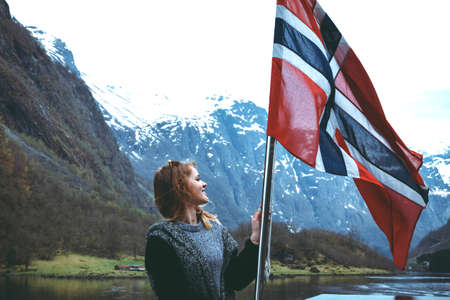 Panorama of fjord. Tourist girl with the flag of Norway enjoys a beautiful view of the fjord and mountains