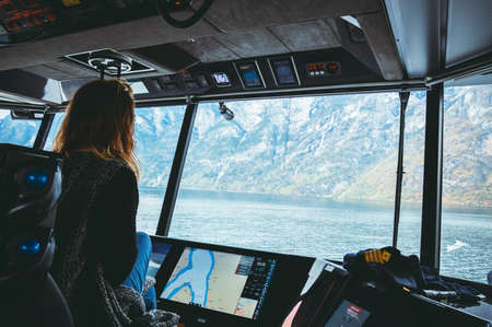 Traveller girl manages the ferry, looking at the river and view of the fjord and mountains, travel and active lifestyle concept