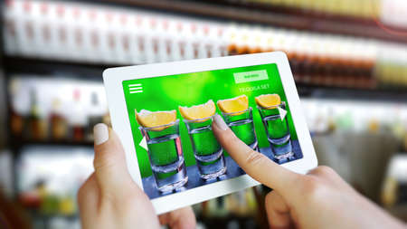 Customer use AR application to order drink at the bar, Hand touching virtual interface for order menu in restaurant, Augmented reality with electronic menu for restaurant. Imagens